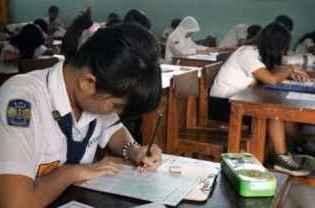 Siswi mengerjakan soal ujian nasional